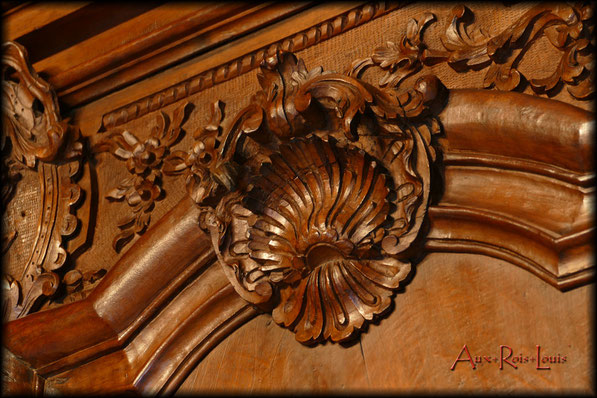 La façade de l'armoire est généreusement ornée de coquilles et de feuillages.
