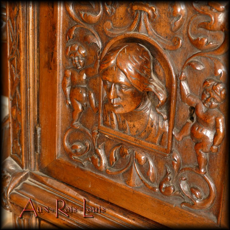 On the doors and sides, sculpted portraits represent the faces of the sponsors of this walnut dresser.